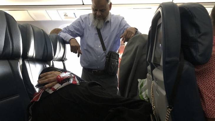 Man stand so wife can sleep on plane