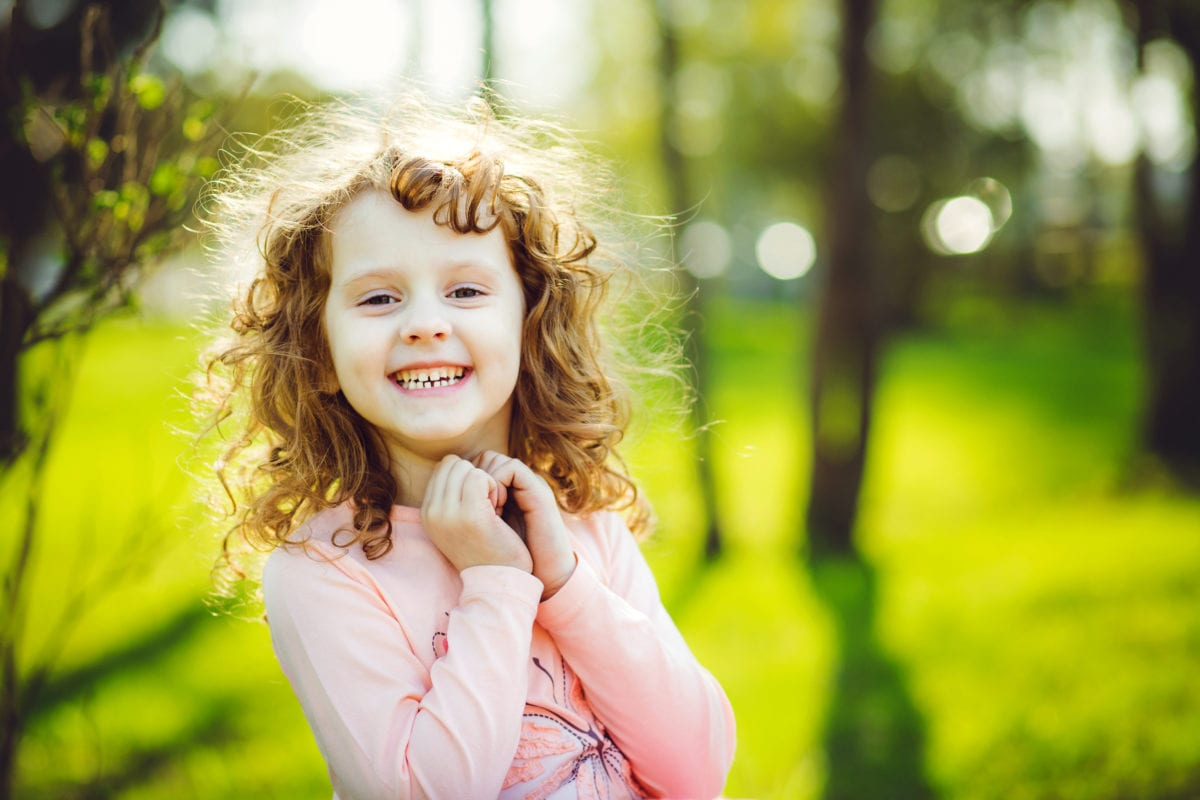 Smiling curly haired girl 30 Irish-Inspired Baby Names for Boys and Girls
