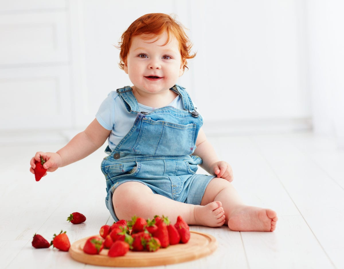 Red haired girl eating strawberries 30 Irish-Inspired Baby Names for Boys and Girls