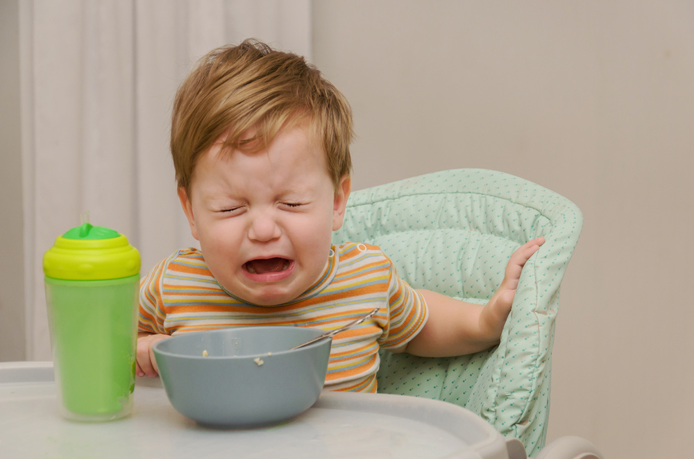 my 10-month-old won't hold his bottle — or really bring anything to his mouth: should i be concerned?
