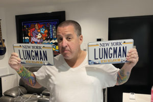 "Dr. Noah Greenspan holding his ""Lungman"" NY license plates in his NYC offices of his Pulmonary Wellness Foundation"