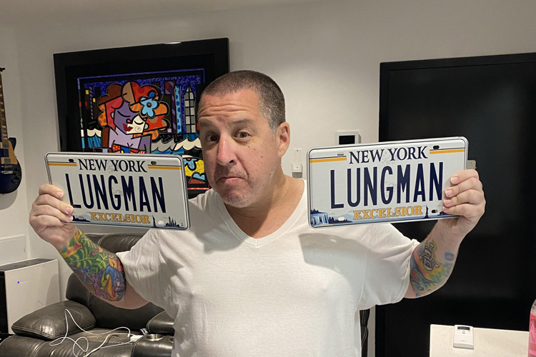 """Dr. Noah Greenspan holding his """"Lungman"""" NY license plates in his NYC offices of his Pulmonary Wellness Foundation"""