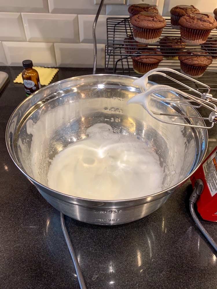 S'more cupcake recipe whipping egg whites in a bowl with hand mixer